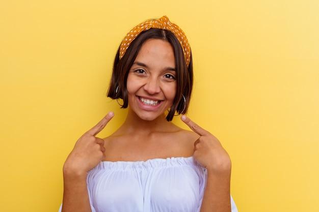 Jeune femme métisse isolée sur le mur jaune sourit, pointant du doigt la bouche.