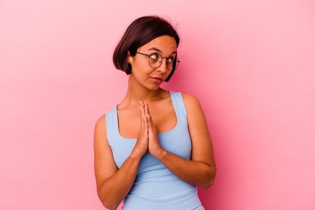 Jeune femme métisse isolée sur mur rose priant, montrant la dévotion, personne religieuse à la recherche d'inspiration divine.
