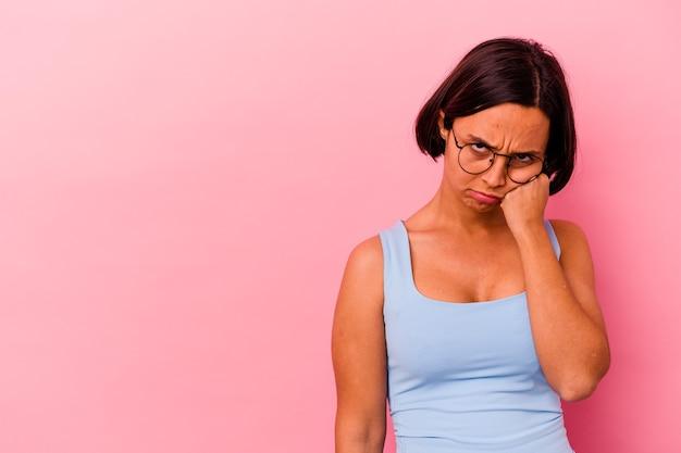 Jeune femme métisse isolée sur un mur rose qui se sent triste et pensif, regardant l'espace de copie.