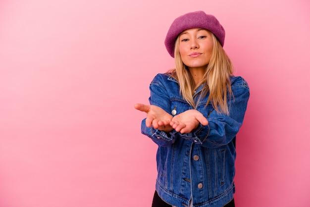 Jeune femme métisse isolée sur le mur rose se pliant les lèvres et tenant les paumes pour envoyer l'air baiser.