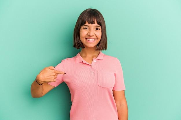 Jeune femme métisse isolée sur une personne bleue pointant à la main vers un espace de copie de chemise, fière et confiante