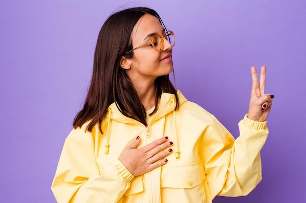 Jeune femme métisse isolée en prêtant serment, mettant la main sur la poitrine.