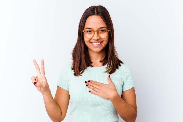 Jeune femme métisse isolée prêtant serment, mettant la main sur la poitrine.