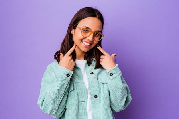 Jeune femme métisse isolée sourit, pointant du doigt la bouche.