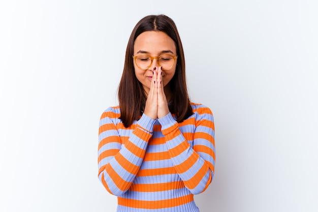 Jeune femme métisse isolée tenant la main dans la prière près de la bouche, se sent confiante.