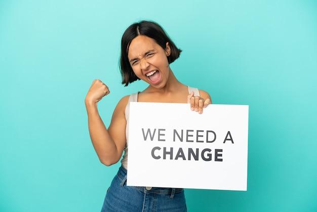 Jeune femme métisse isolée tenant une pancarte avec du texte nous avons besoin d'un changement et faisant un geste fort