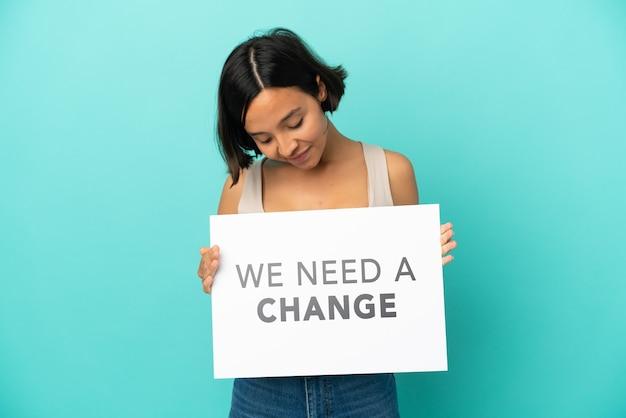 Jeune femme métisse isolée tenant une pancarte avec du texte nous avons besoin d'un changement