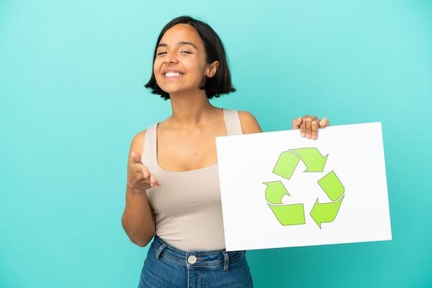 Jeune femme métisse isolée tenant une pancarte avec l'icône de recyclage faisant un accord
