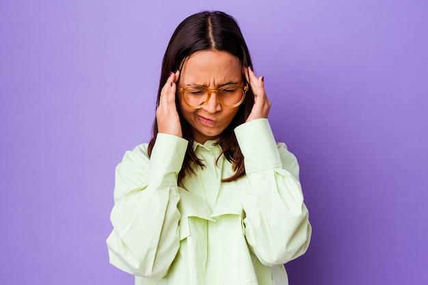 Jeune femme métisse isolée touchant les temples et ayant des maux de tête.