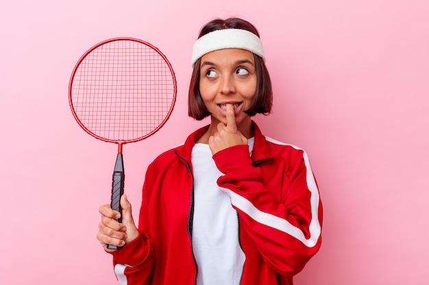 Jeune femme métisse jouant au badminton isolé sur un mur rose détendu en pensant à quelque chose en regardant un espace de copie.