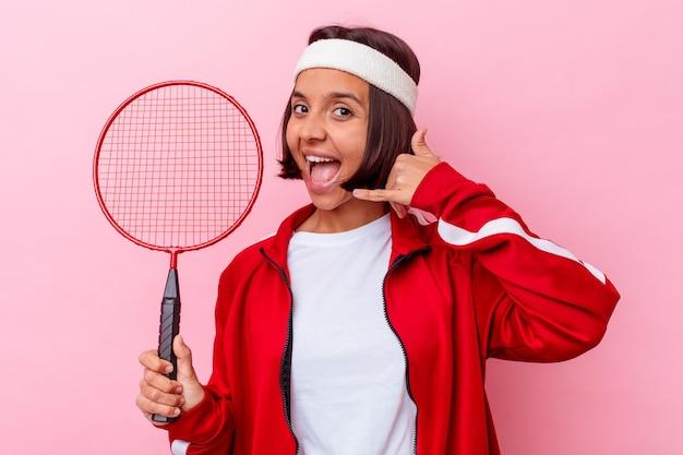 Jeune femme métisse jouant au badminton isolé sur un mur rose montrant un geste d'appel de téléphone mobile avec les doigts.