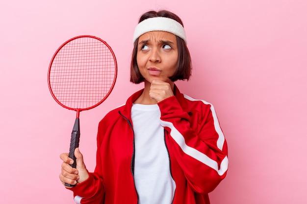 Jeune femme métisse jouant au badminton isolé sur un mur rose à la recherche de côté avec une expression douteuse et sceptique.