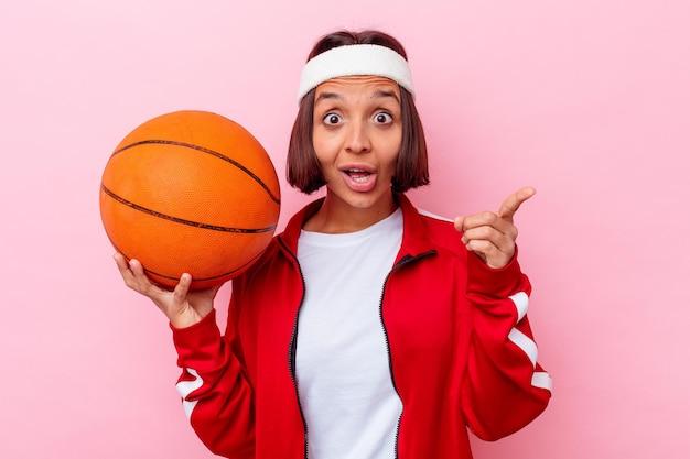 Jeune femme métisse jouant au basket-ball isolé sur un mur rose ayant une idée, un concept d'inspiration.