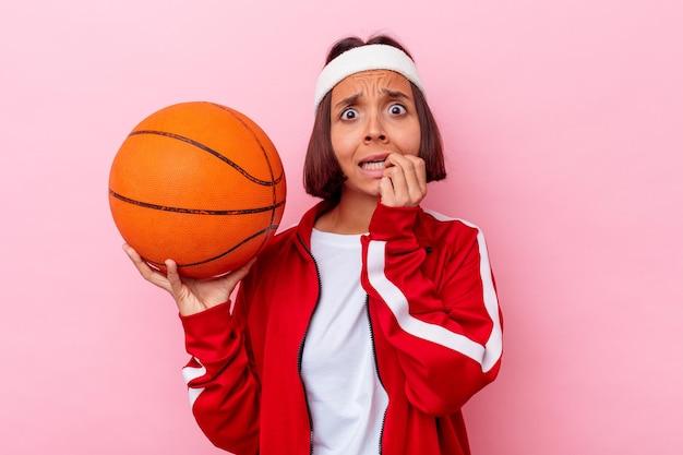 Jeune femme métisse jouant au basket isolé sur mur rose se mordant les ongles, nerveuse et très anxieuse.
