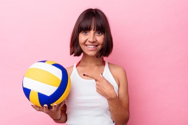 Jeune femme métisse jouant au volley-ball isolée sur fond rose souriante et pointant de côté, montrant quelque chose dans un espace vide.