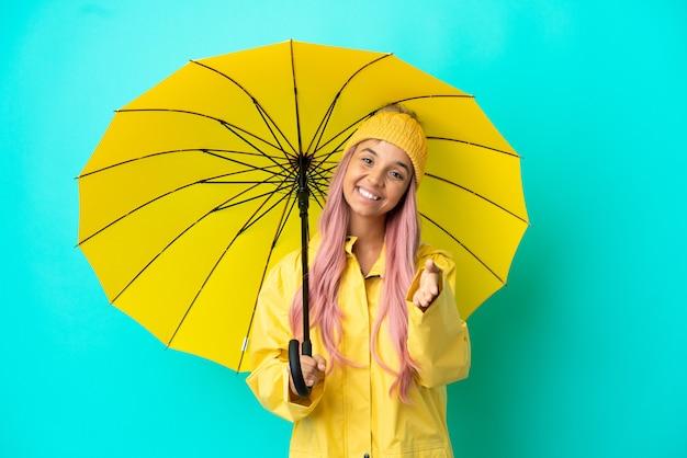 Jeune femme métisse avec manteau imperméable et parapluie se serrant la main pour conclure une bonne affaire