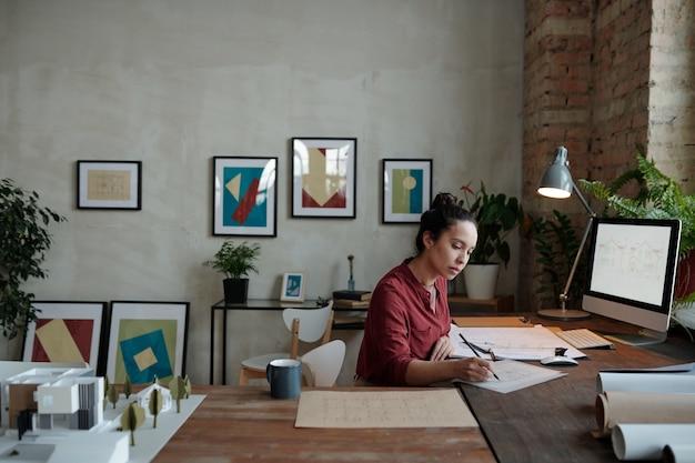 Jeune femme métisse occupée avec un chignon assis au bureau et dessinant un croquis tout en travaillant au bureau avec des photos sur le mur