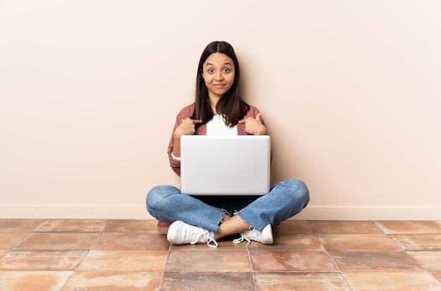 Jeune femme métisse avec un ordinateur portable assis sur le sol avec une expression faciale surprise