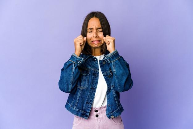 Jeune femme métisse pleurnichant et pleurant de façon inconsolable.
