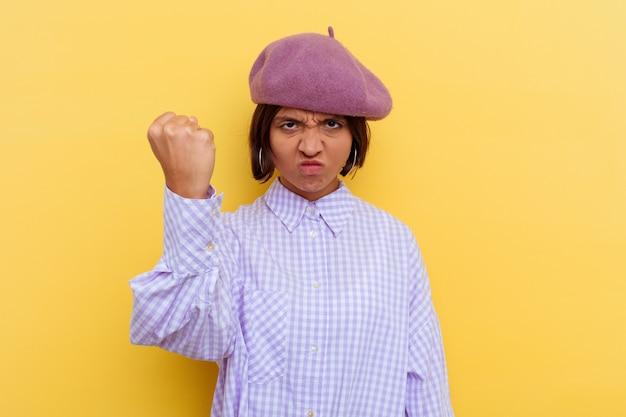 Jeune femme métisse portant un béret isolé sur fond jaune montrant le poing à la caméra, expression faciale agressive.