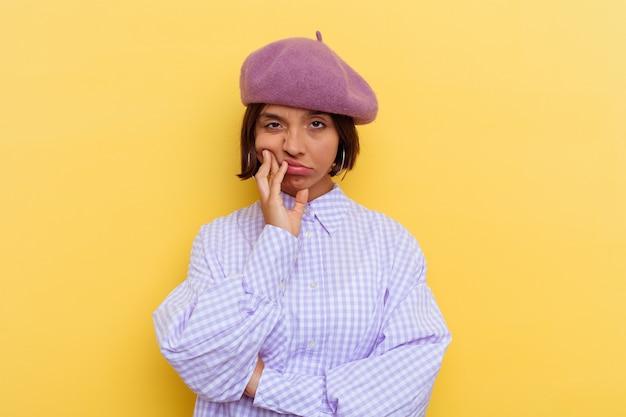 Jeune femme métisse portant un béret isolé sur fond jaune qui s'ennuie, est fatiguée et a besoin d'une journée de détente.