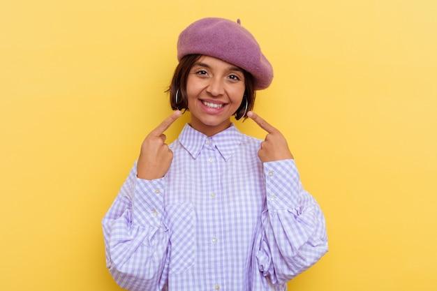 Jeune femme métisse portant un béret isolé sur fond jaune sourit, pointant du doigt la bouche.