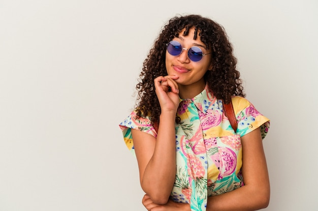 Jeune femme métisse portant des lunettes de soleil prenant des vacances isolées regardant de côté avec une expression douteuse et sceptique.