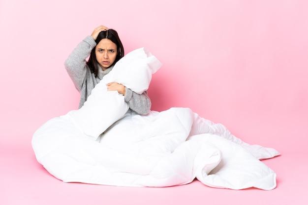 Jeune femme métisse portant pijama assis sur le sol avec une expression de frustration et de ne pas comprendre