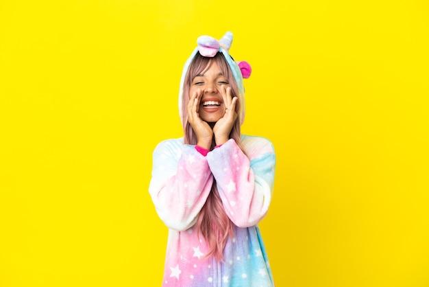 Jeune femme métisse portant un pyjama licorne isolé sur fond blanc criant et annonçant quelque chose