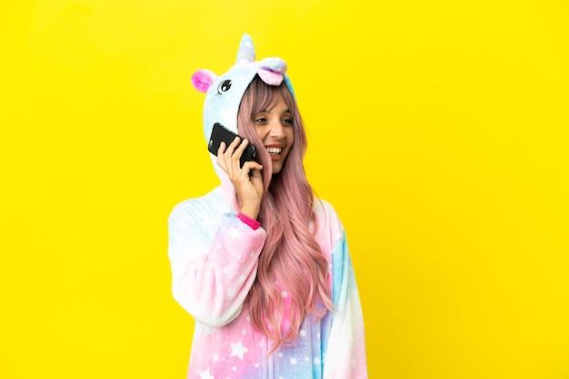 Jeune femme métisse portant un pyjama licorne isolé sur fond blanc en gardant une conversation avec le téléphone mobile