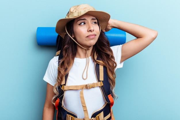 Jeune femme métisse de randonneur isolée sur fond bleu touchant l'arrière de la tête, pensant et faisant un choix.
