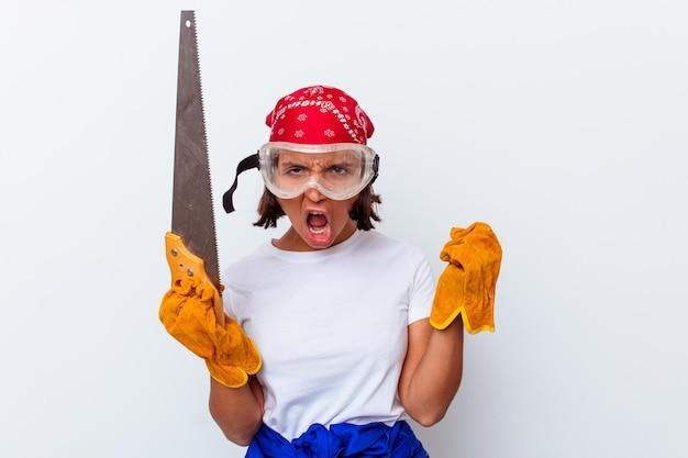 Jeune femme métisse réparant sa maison avec une scie isolée sur un mur blanc