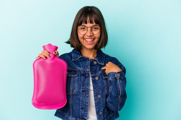Jeune femme métisse tenant une bouteille d'eau chaude isolée sur fond bleu personne pointant à la main vers un espace de copie de chemise, fière et confiante