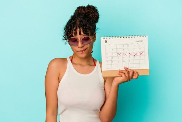 Jeune femme métisse tenant un calendrier isolé sur fond bleu confus, se sent dubitative et incertaine.