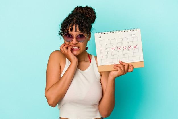 Jeune femme métisse tenant un calendrier isolé sur fond bleu se ronger les ongles, nerveuse et très anxieuse.