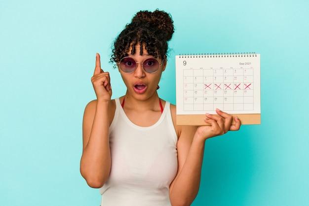 Jeune femme métisse tenant le calendrier isolé sur un mur bleu ayant une idée, un concept d'inspiration.