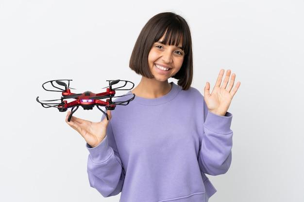 Jeune femme métisse tenant un drone isolé sur fond blanc saluant avec la main avec une expression heureuse