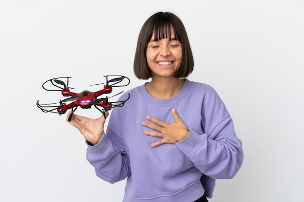 Jeune femme métisse tenant un drone isolé sur fond blanc souriant beaucoup