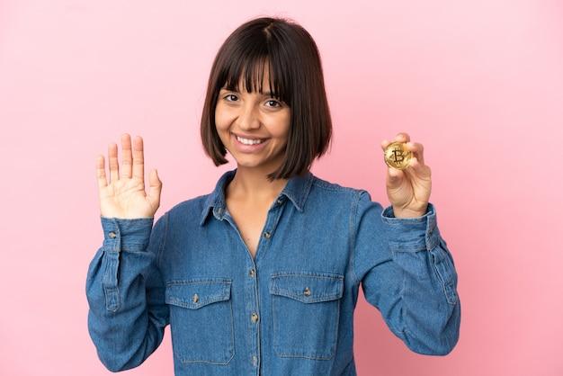 Jeune femme métisse tenant un fond isolé bitcoin saluant avec la main avec une expression heureuse