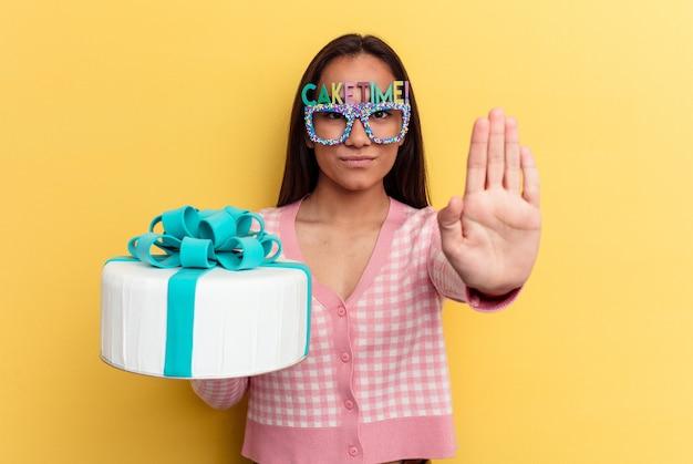 Jeune femme métisse tenant un gâteau isolé sur fond jaune debout avec la main tendue montrant un panneau d'arrêt, vous empêchant.