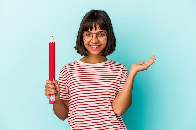 Jeune femme métisse tenant un gros crayon isolé sur fond bleu montrant un espace de copie sur une paume et tenant une autre main sur la taille.