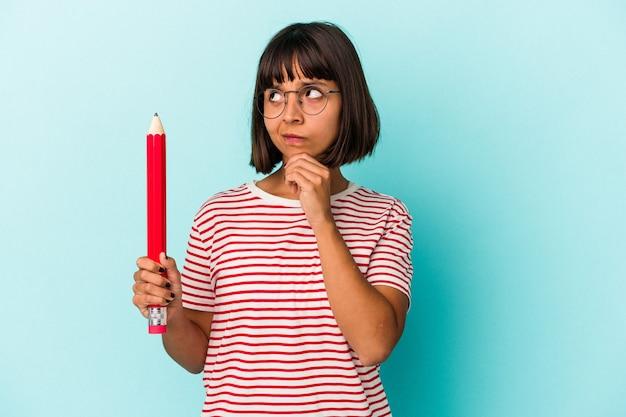 Jeune femme métisse tenant un gros crayon isolé sur fond bleu regardant de côté avec une expression douteuse et sceptique.