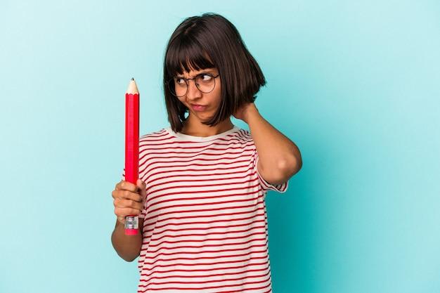 Jeune femme métisse tenant un gros crayon isolé sur fond bleu touchant l'arrière de la tête, pensant et faisant un choix.