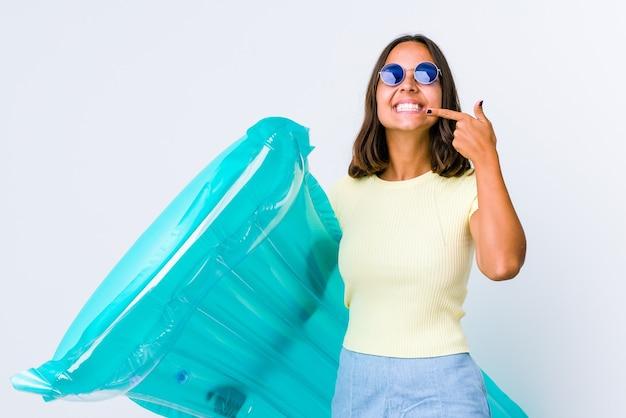 Jeune femme métisse tenant un matelas pneumatique sourit, pointant du doigt la bouche.