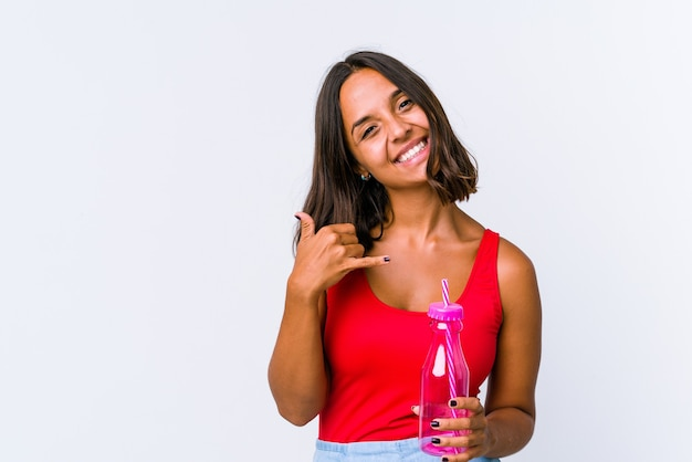 Jeune femme métisse tenant un milk-shake isolé montrant un geste d'appel de téléphone portable avec les doigts.