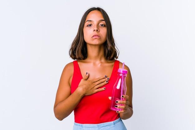 Jeune femme métisse tenant un milk-shake isolé prêtant serment, mettant la main sur la poitrine.