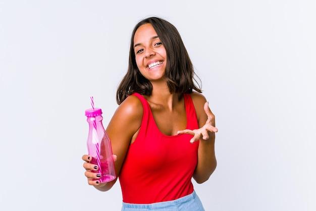 Jeune femme métisse tenant un milk-shake isolé se sent confiant en donnant un câlin à la caméra.