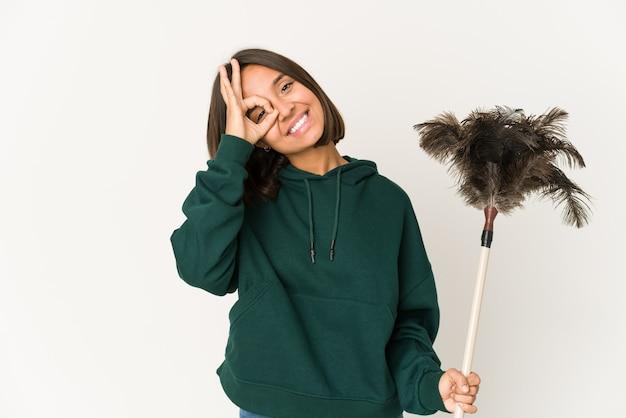 Jeune femme métisse tenant un plumeau isolé
