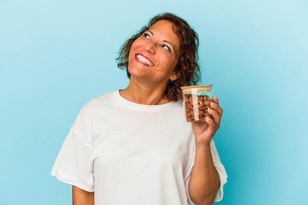 Jeune femme métisse tenant un pot d'amande isolé sur fond bleu rêvant d'atteindre des objectifs et des objectifs