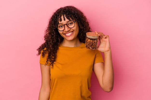 Jeune femme métisse tenant un pot d'amande isolé sur fond rose heureux, souriant et joyeux.